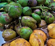 Green and yellow coconuts. On the heap in market Stock Photography
