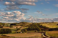Green and yellow countryside under blue skies with white clouds. And winding roads Royalty Free Stock Images