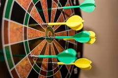 Green and Yellow Darts on Brown-black-green-and-red Dartboard Stock Photo