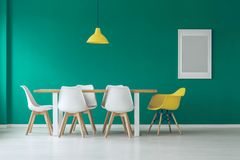 Green and yellow dining room. Grey poster in green and yellow dining room interior with lamp above wooden table and white chairs Royalty Free Stock Image