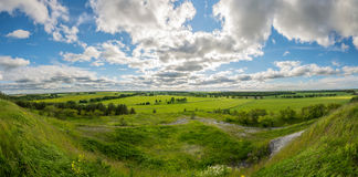 Green, yellow field forest and clouds on blue sky in summer, sunny day. Stock Image