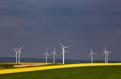 Green and yellow fields with Wind turbines generating electricity. Wind turbines before the thunderstorm. Spring sunny day on green field with wind power royalty free stock photography