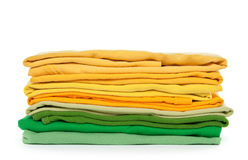 Green and yellow folded clothes. Spring colors. Green and yellow folded clothes on white background royalty free stock images