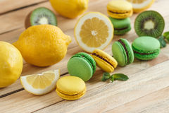 Green and yellow french macarons with kiwi, lemon and mint decorations Royalty Free Stock Photography