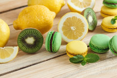 Green and yellow french macarons with kiwi, lemon and mint decorations Royalty Free Stock Images