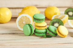 Green and yellow french macarons with kiwi, lemon and mint decorations Stock Photography