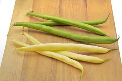 Fresh beans on a wooden board. Green and yellow fresh beans on a wooden board Stock Photography