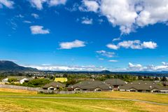 Green and yellow grass lawn, roofs of the houses and the view of Taupo town. In New Zealand Royalty Free Stock Photography