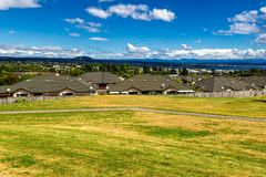 Green and yellow grass lawn, roofs of the houses and the view of Taupo town. In New Zealand Royalty Free Stock Photo