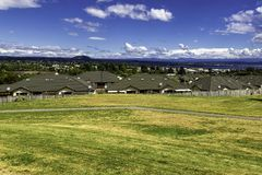 Green and yellow grass lawn, roofs of the houses and the view of Taupo town, New Zealand. Green and yellow grass lawn, roofs of the houses and the view of Taupo Stock Image