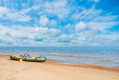 Green and yellow inflatable boat with oars standing at the sandy. Beach coast with wavy seascape and beautiful dramatic blue cloudy sky on sunny day. Vacation Stock Image