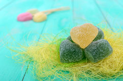 Green and yellow jelly candy heart shaped sugar decoration on a bright spring background Stock Photos