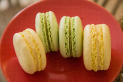Green and yellow macaroons over red plate Royalty Free Stock Image