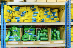 Green, yellow nylon soft lifting slings stacked in piles. Royalty Free Stock Photos