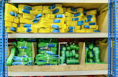 Green, yellow nylon soft lifting slings stacked in piles. Royalty Free Stock Images