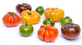 Green, yellow, orange and purple tomatoes. On white Royalty Free Stock Photo