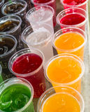 Green yellow orange red black soft drink. In plastic glass Stock Images
