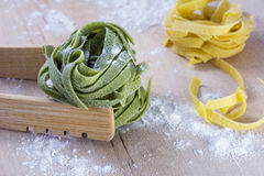 Green and yellow pasta on wooden table with flour. Green and yellow pasta on wooden table with white flour Stock Photography