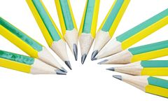 Green and yellow pencils alternating in semicircle shape. Close up Green and yellow pencils alternating in semicircle shape stock images