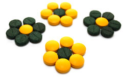 Green and yellow pills in the form of flowers Royalty Free Stock Photography