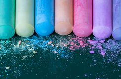 Multicolored crayons, pastel. Green, yellow, pink, purple, blue. Painted Pastels. Spilled chalk on a green board Royalty Free Stock Photography