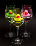 Green, yellow and pink rubber ducks in wineglasses Stock Images