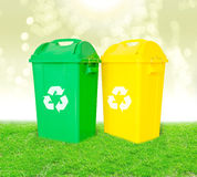Green and yellow plastic trash recycling container with recycle Stock Photo