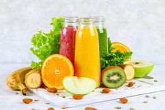 Green, yellow, purple smoothies in currant bottles, parsley, app. Le, kiwi, orange on a gray table Stock Photo