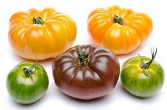 Green, yellow and purple tomatoes. On white Royalty Free Stock Photography