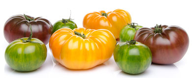 Green, yellow and purple tomatoes. On white Royalty Free Stock Photos