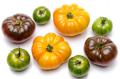 Green, yellow and purple tomatoes. On white Stock Image