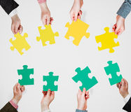 Green and yellow puzzle pieces in people hands Stock Photo