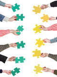 Green and yellow puzzle pieces in people hands Stock Photography