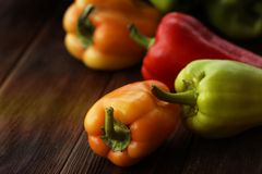Green , yellow and red bell pepper on wooden background stock image