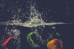 Green Yellow Red bell peppers drop into the water with splash. Royalty Free Stock Photos