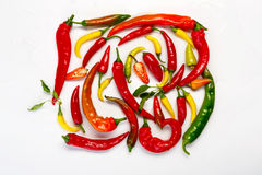 Green, yellow and red chili peppers isolated on white background. Plenty of green, yellow and red chili pepper isolated on white background. Closeup pile of Stock Images