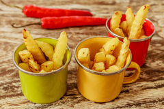 Green, yellow and red enameled cups with potato fries decorated with a red chilly pepper, over wooden table. Side view. Royalty Free Stock Photo