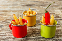 Green, yellow and red enameled cups with potato fries decorated with two cherry tomatoes, basil leaves, over wooden table. Stock Image