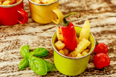 Green, yellow and red enameled cups with potato fries decorated with two cherry tomatoes, basil leaves and a red chilly pepper Royalty Free Stock Image