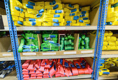 Green, yellow and red nylon soft lifting slings stacked in piles. Warehouse of finished products for industrial enterprises Royalty Free Stock Images