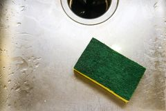 Green and yellow scrubing sponge lying in scratch and wet sink with garage disposal Stock Photography