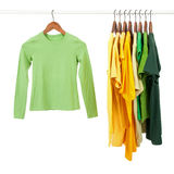 Green and yellow shirts on wooden hangers. Green and yellow casual shirts on wooden hangers, isolated on white royalty free stock image