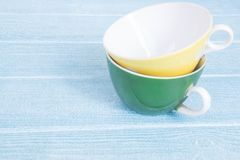 Yellow and green cups on the blue background stock photos