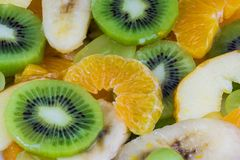 Close-up of sliced kiwis and oranges on a fruit salad background royalty free stock image