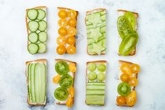 Green and yellow vegetables sandwiches. Variety of sandwiches with cream cheese, cucumbers and tomatoes on a light background. Top view, flat lay, overhead Stock Photos