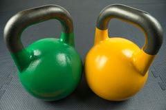 Green and yellow weightlifting kettlebells in a gym. Exercise / fitness assessment / new year resolution concept royalty free stock photography
