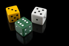 Green, yellow and white dices on black background stock photography