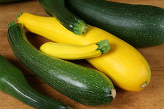 Green and yellow zucchini. Fresh vegetables from the organic farm. Yellow and green zucchini on the old board Stock Images