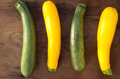 Green and yellow zucchini on wooden background.  Stock Image