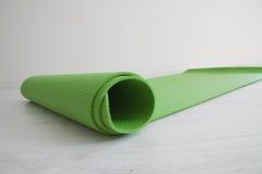 Green yoga carpet. Twisted green yoga carpet on a floor Stock Photo
